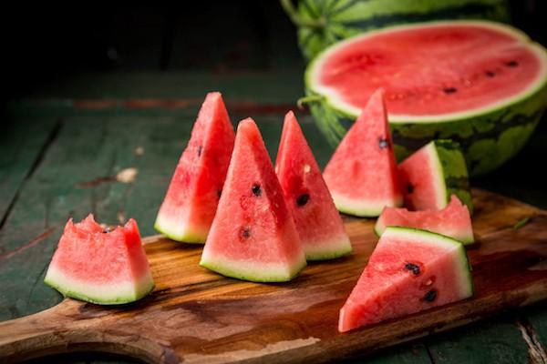 Fél görögdinnye, mellette háromszög alakúra vágott cikkek a gyümölcsből.