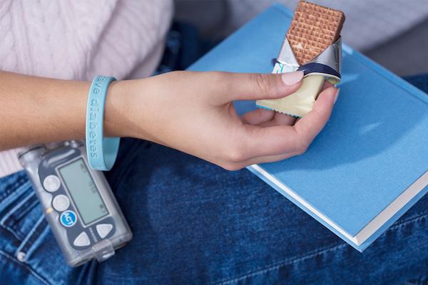 Diabéteszes fiatal lány vércukorszintmérővel, diétás csokival a kezében.