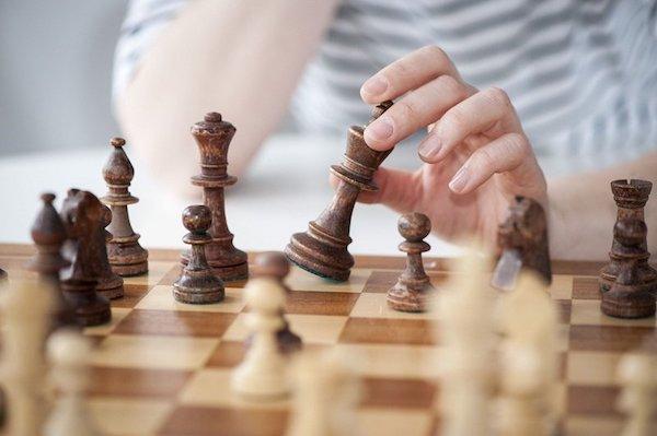 Sakktáblán a királlyal fontolgatja lépését egy hölgy.