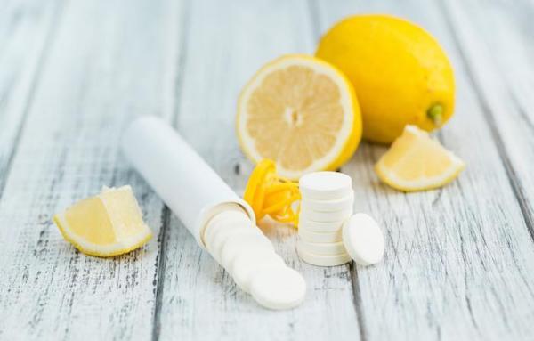 C-vitamin tabletta formájában, mellette citromgerezdek és egy egész citrom.