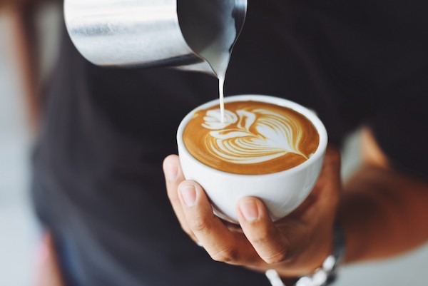 Barista tejszínt önt egy csésze kávéba mintát formázva belőle.