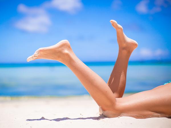 Tengerparton a homokban fekvő nő felmeli a lábát hason fekve.