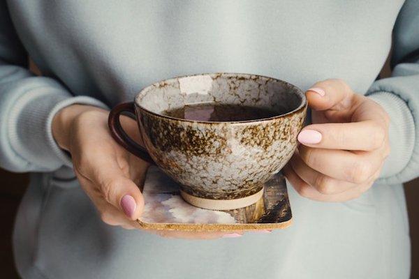 Egy csésze teát tart kezében egy hölgy.