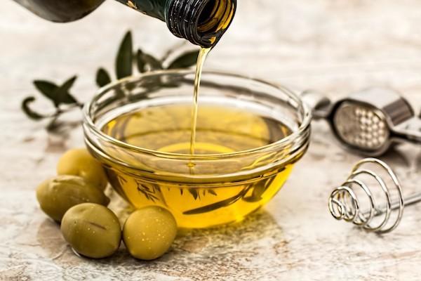 Olívaolajat öntenek egy kis tálba, amely mellett olívabogyók vannak.