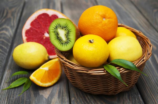 C-vtiaminban gazdag gyümölcsök egy fonott kosárban: citrom, narancs, grépfrút és kivi.