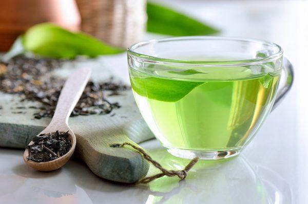 Szemes zöld tea fakanálban, mellette egy csésze zöld tea.