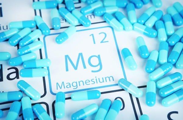 Magnéziumkapszulák egy kémiai táblázaton a magnézium vegyjele körül.