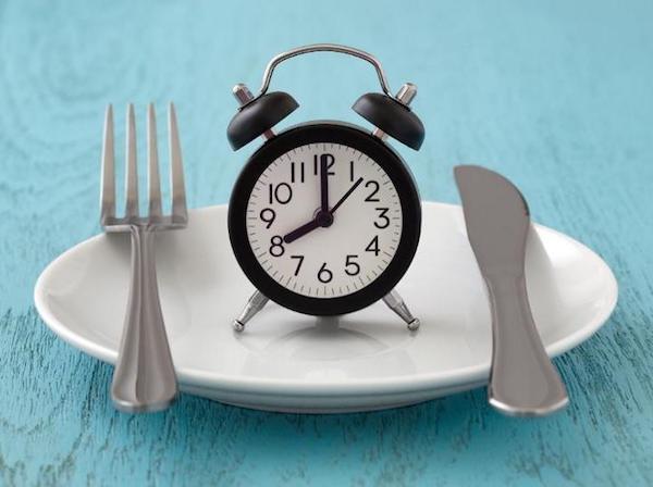 Üres tányéron egy óra, mellette kés és villa.