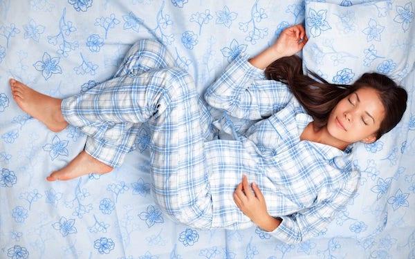 Pizsamában alszik egy fiatal nő az ágyában.