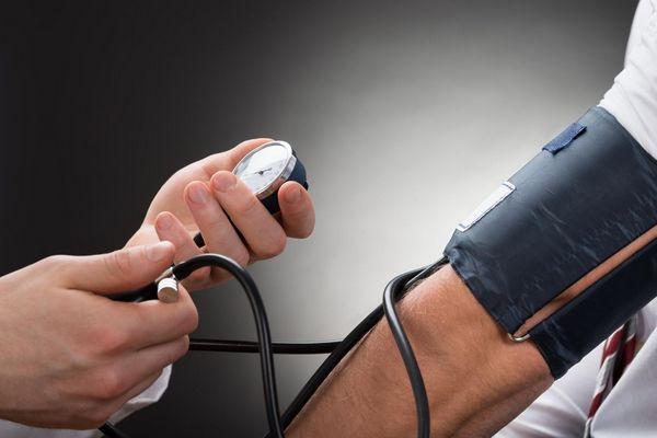 Orvos méri a beteg vérnyomását, vérnyomásmérés orvosi rendelőben.