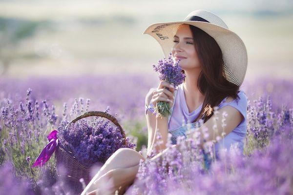 Levendulamezőn ülő fiatal lány szalmakalappal, kezében levendula-virágcsokorral.
