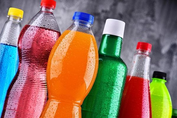 Színes cukros üdítőitalok műanyag palackokban, színes cukrozott italok egymás mellett.