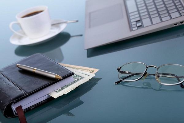 Íróasztalon laptop, határidőnapló, szemüveg és egy csésze kávé.