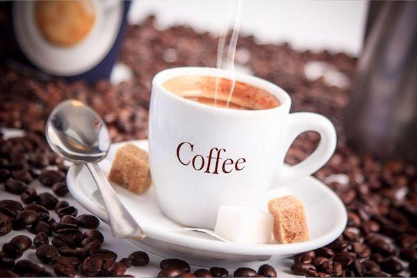 Gőzölgő kávé fehér kávéscsészében barna és fehér cukorral, kávéskanállal, sok kávébabszemmel körülvéve.