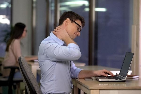 Irodában dolgozó férfi fogja a fájós nyakát, ülőmunkát végző férfi az irodában megmasszírozza a nyakát.