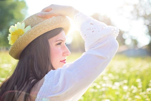 Szalmakalapban lévő hölgy a napfényes réten.