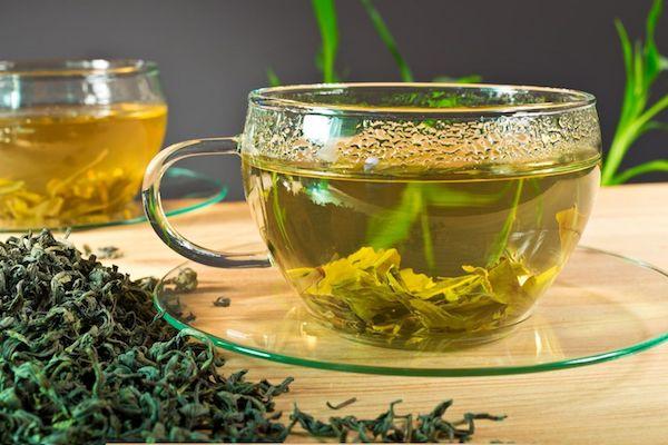 Üveg teáscsészék tele zöld teával, szárított zöldtea-levelek egy teáscsésze mellett.