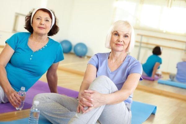 Két 50 feletti hölgy edzésre vár a jógaszőnyegén.