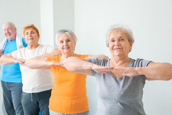 Idős, nyugdíjas emberek jókedvűen tornáznak.