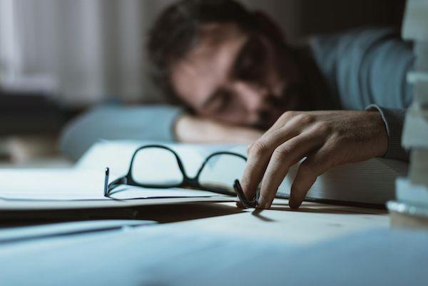 Férfi alszik munka közben egy könyvre ráhajolva, kezében fogja a szemüvegét.