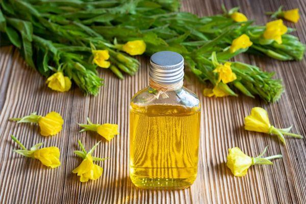 Ligetszépe virágai és ligetszépe-olaj kis üvegben egy asztalon.