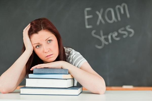 Egyetemista lány stresszes, aggódó arckifejezéssel könyveire hajolva fogja a fejét.