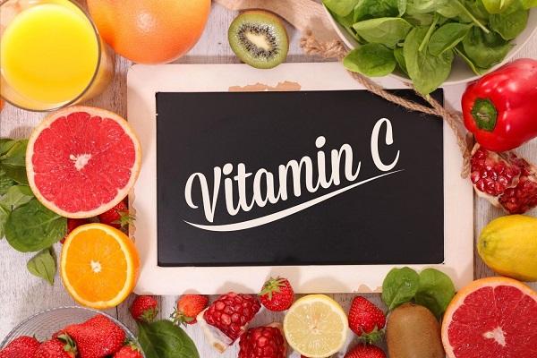 C-vitamin felirat egy táblán, körülötte egész és félbevágott gyümölcsök és zöldségek, narancs, eper, kivi, citrom, grépfrút, paprika, spenót.