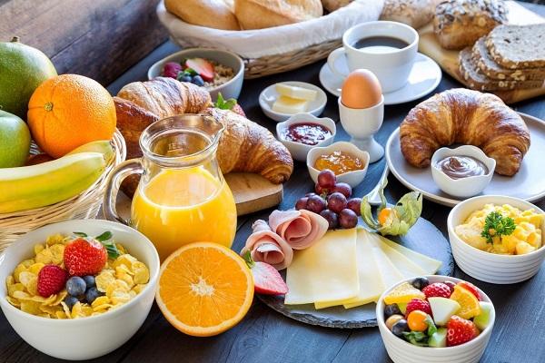 Bőséges reggeli egy asztalon: gyümölcsök, müzli, péksütemények, tojás, lekvár, narancslé, vaj, felvágott.