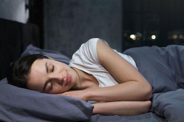Fiatal lány oldalán fekve békésen alszik sötétszürke ágyneműben.