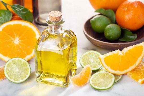 Citrusillóolaj üvegben, valamint egész és félbevágott citromok és narancsok az asztalon.