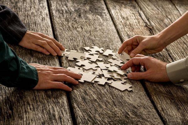 Emberi kezek egy asztalra kiborított puzzle-halomból kivesznek egyes darabokat .