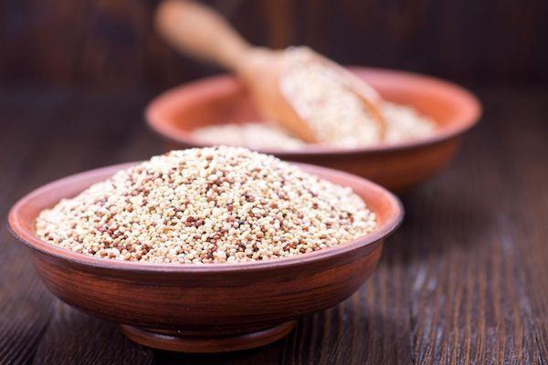 Fából készült asztalon két tálban púposra halmozott quinoa, a hátul levő tálban fakanál is található.