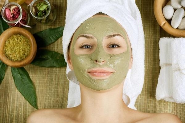 Fiatal lány kozmetikában fekszik, arcán zöld színű arcpakolás, haja fehér törölközőbe csavarva.