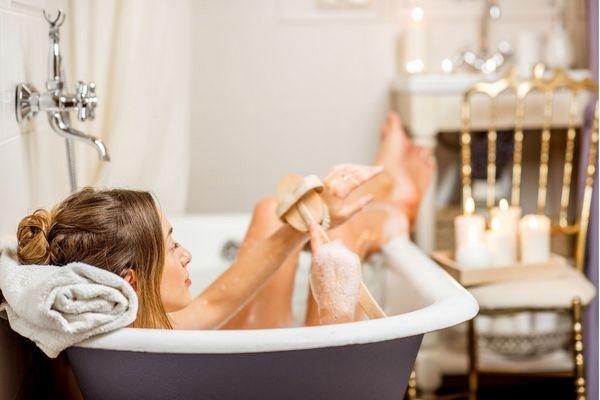 Fiatal hölgy forró kádfürdőt vesz, tisztogatja magát.