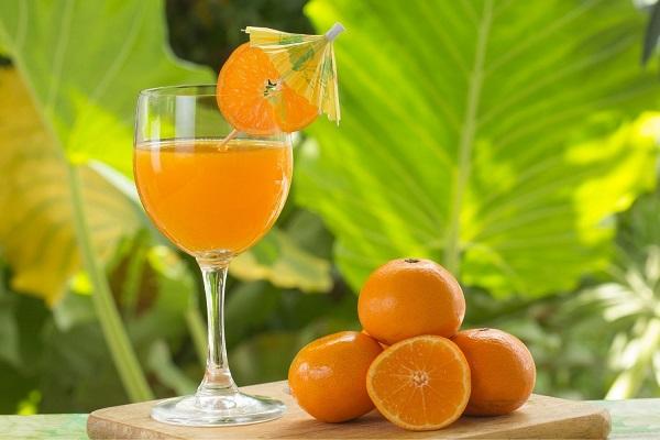 Egész és félbevágott narancsok, mellettük frissen facsart narancslé egy üvegpohárban.