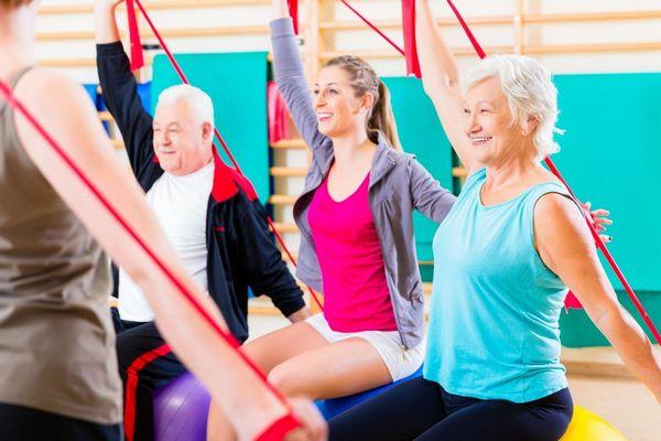 Mosolygós idős emberek nyújtógyakorlatokat végeznek egy tornateremben.
