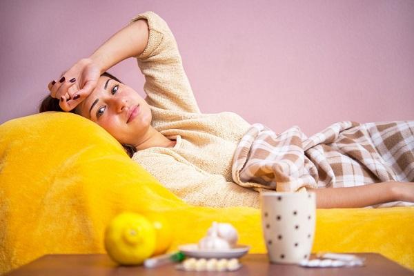 Fiatal hölgy betegen ágyában fekszik, kezét a fájós fejére teszi, mellette a gyógyszerei, hőmérő, bögre, citrom és fokhagyma.