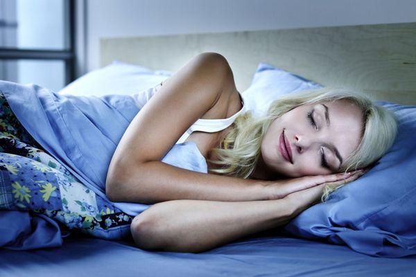 Fiatal hölgy oldalán fekve alszik az ágyban, mosolyog álmában.