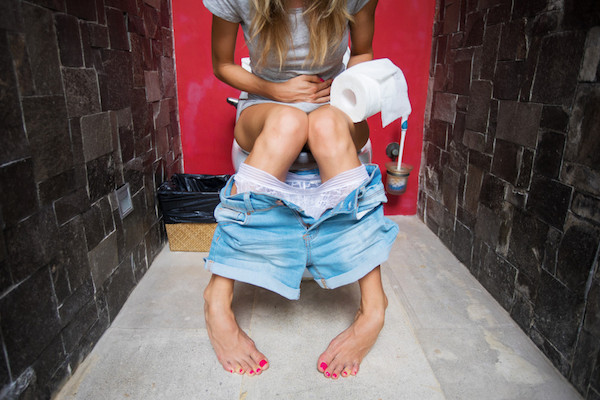 Fiatal lány hasmenéssel ül a WC-n.