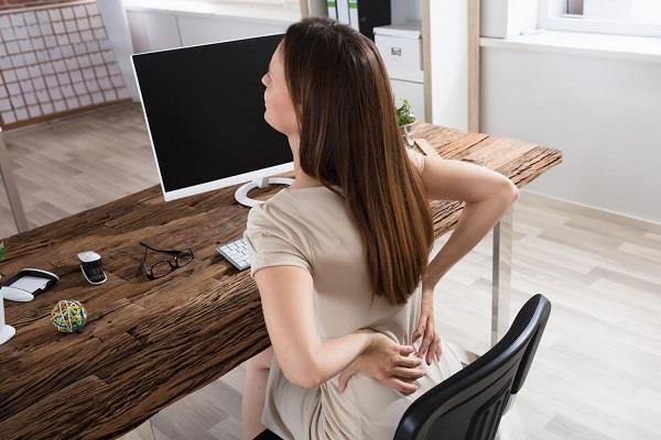 Fiatal nő íróasztalnál ülve dolgozik, derékfájdalom miatt kezével a hátát fogja.