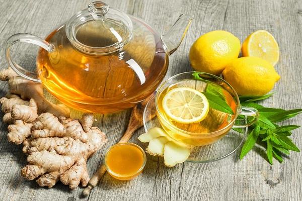 Gyömbértea egy üveg teáskannában és üveg csészében, mellette gyömbérgyökerek, egész és félbevágott citromok és méz.