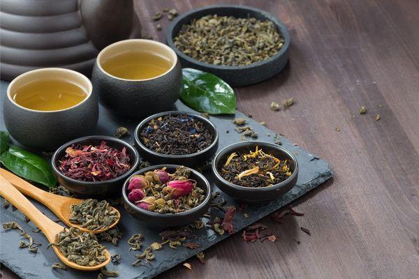 Fekete, zöld és gyümölcsteák kis tálakban és fakanalakban, mellettük két csésze forró teával.