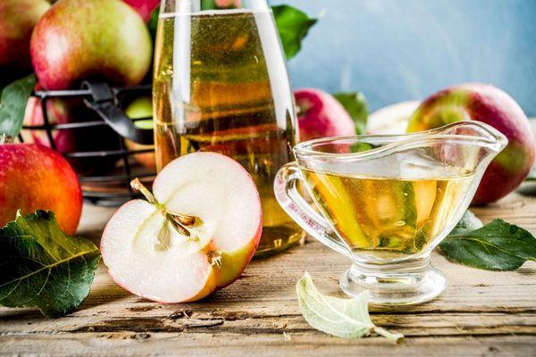 Egész és félbevágott almák egy asztalon, mellettük almaecet üvegben és üvegkiöntőben.