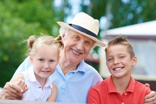 Boldog idős, nyugdíjas férfi két unokája körében.