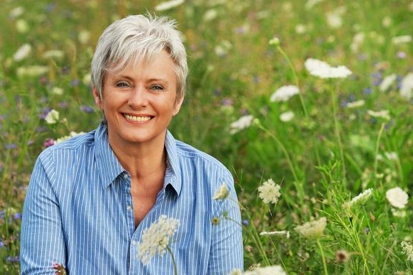 Menopauzába lépett középkorú, ősz hajú hölgy mosolyogva ül egy virágos réten.
