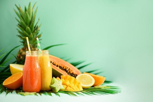 Egész ananász, valamint félbevágott papaja, citrom, narancs és csillagvirág, mellette ananászlevet és papajalevet tartalmazó üvegek.