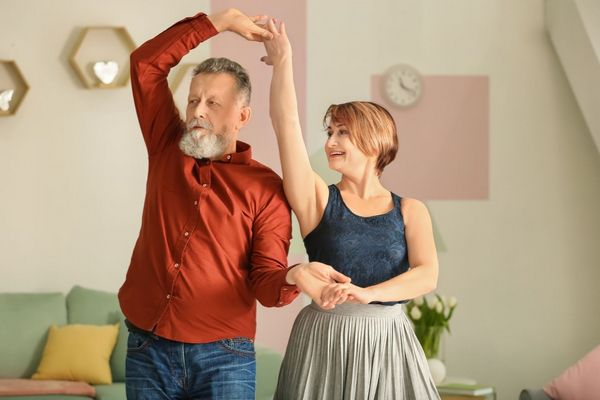 Nyugdíjas házaspár az otthonában táncol.