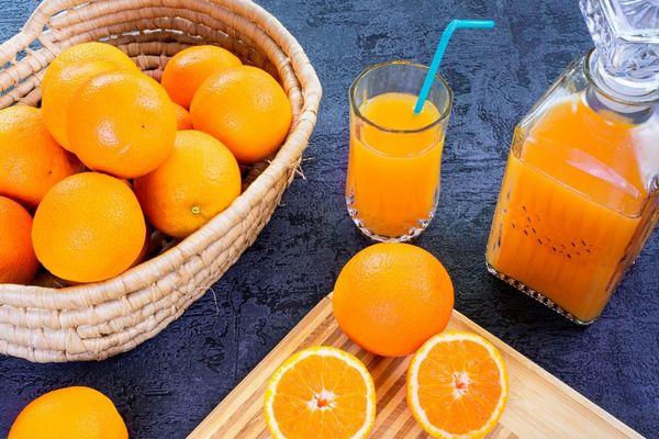 Kosárban elhelyezett narancsok, mellette egész és félbevágott narancsok, valamint üvegpohárban és kancsóban narancslé.