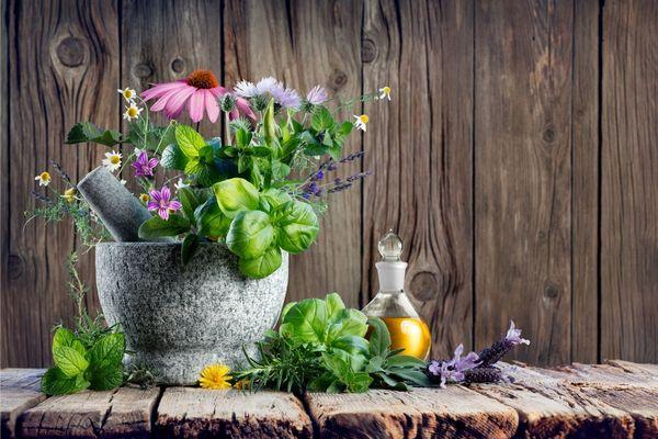 Illóolajos üveg, mellette kőmozsárban gyógynövények: bazsalikom, bíbor kasvirág, menta, kamilla, levendula, citromfű és rozmaring.