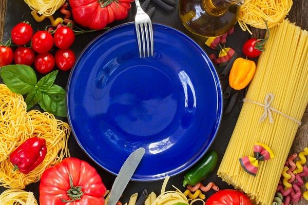 Kék színű tányér száraztésztával, paradicsommal, paprikával, bazsalikommal körülvéve egy asztalon.